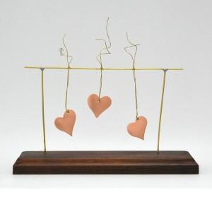 Τρεις καρδιές κρεμαστές σε ξύλινη βάση